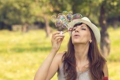 Den unga nätta caucasian kvinnan som har gyckel med att blåsa, bubblar Royaltyfri Foto