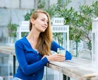 Den unga nätta kvinnan dricker coctailen Fotografering för Bildbyråer