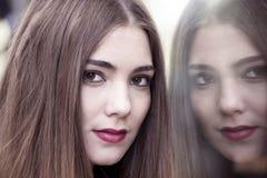 Den unga och attraktiva framsidan för hipsterkvinna` s reflekterar på shoppingfönstret fotografering för bildbyråer