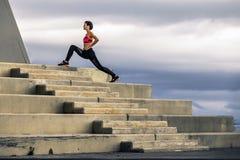 Den unga och attraktiva kvinnan i sportswear gör utfall som står på trappan Royaltyfria Foton
