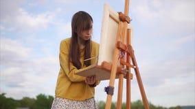 Den unga och idérika konstnären målar en bild på kanfas i en öppen luft stock video