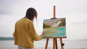 Den unga och idérika konstnären målar en bild på kanfas i en öppen luft arkivfilmer