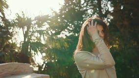 Den unga och nätta kvinnan är i en tropisk skog med palmträd i dagen lager videofilmer