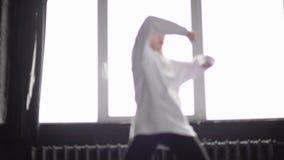 Den unga och stilfulla flickan i vit beklär danshöftflygtur i ultrarapid stock video