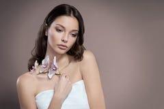 Den unga och sunda kvinnan med ljust smink rymmer orkidéblomman Beige bakgrund Arkivfoton