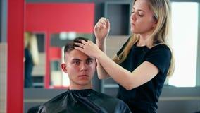 Den unga och yrkesmässiga hårstylisten gör utforma med som stelnar, och annat utforma lager videofilmer