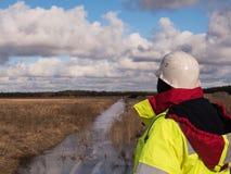 Den unga ordföranden At Construction Site kontrollerar pågående produktion i svåra kalla villkor royaltyfri foto