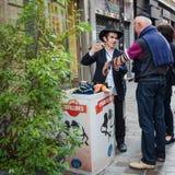 Den unga ortodoxa judiska mannen diskuterar Tefillinen med en förbipasserande Royaltyfri Foto