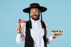 Den unga ortodoxa judiska mannen med den svarta hatten med Hamantaschen kakor för judisk festival av Purim arkivfoto