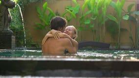 Den unga den parkvinnan och mannen har gyckel i deras privata simbassäng Br?llopsresabegrepp arkivfilmer