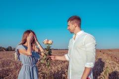 Den unga parmankvinnan, sommarvetefält, lyckligt le ger gåvan, buketten av rosor, överraskningerbjudande Hallon i en hj?rtaform royaltyfri foto