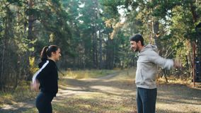 Den unga den parmannen och kvinnan gör sportar utomhus parkerar in att snurra armar och att le tycka om uppvärmning och det bra f lager videofilmer