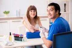 Den unga patienten under tillvägagångssätt för provtagning för blodprov royaltyfri fotografi