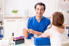 Den unga patienten under tillvägagångssätt för provtagning för blodprov arkivbild