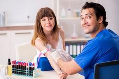 Den unga patienten under tillvägagångssätt för provtagning för blodprov royaltyfria bilder