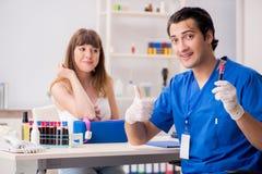 Den unga patienten under tillvägagångssätt för provtagning för blodprov arkivfoto