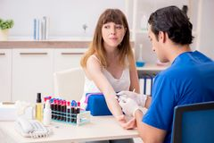 Den unga patienten under tillvägagångssätt för provtagning för blodprov fotografering för bildbyråer