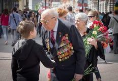 Den unga patrioten talar med den gamla veteran av världskrig II Arkivbilder