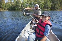 Den unga pojkefiskaren ler på låset av trevliga walleye royaltyfria bilder
