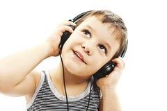 Den unga pojken är le och lyssna till musik som ser upp Arkivbild