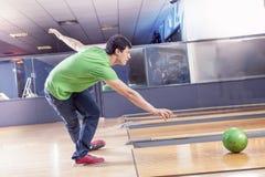 Den unga pojken drar bollen på bowlingbanan Royaltyfri Foto