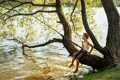 Den unga pojken fiskar, medan sitta på en trädfilial över en flod Royaltyfria Bilder