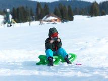 Den unga pojken har gyckel på vintervacatioin och spelar lekar på telefonen Royaltyfri Bild