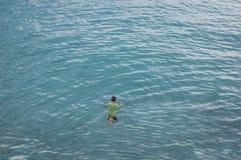 Den unga pojken hoppar in i det blåa havet Arkivfoton