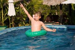 den unga pojken i ett floting gummihjul tycker om nytt pölvatten royaltyfria foton