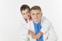Den unga pojken kramar hans fader lovingly Royaltyfri Foto