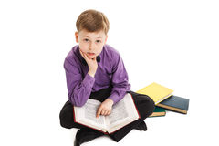 Den unga pojken läser en isolerad bok på vit bakgrund Royaltyfria Bilder