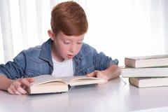 Den unga pojken läser mycket koncentrerat i en bok arkivbild