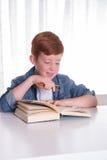 Den unga pojken läser mycket koncentrerat i en bok arkivfoto