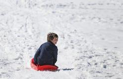 Den unga pojken med brunt hår i vintern spelar med guppar i moen Royaltyfri Fotografi
