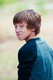 Den unga teen seende kameran med frown vänder mot Arkivbild