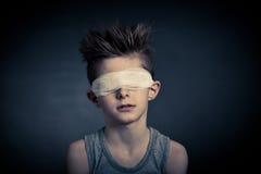 Den unga pojken med förbinder på ögon mot grå färger Royaltyfria Foton