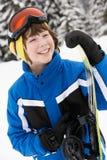 Den unga pojken med snowboarden skidar på ferie arkivbild