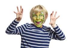 Den unga pojken med vänder mot målningmonster arkivbild