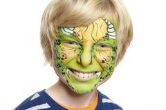 Den unga pojken med vänder mot målningmonster Royaltyfria Bilder