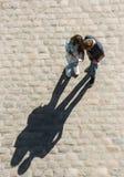Den unga pojken och flickan ser mobiltelefon n gatan arkivfoto