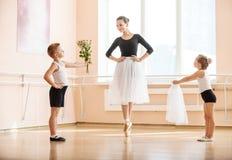 Den unga pojken och flickan som ger blommor och, skyler till äldre student, medan hon dansar en-pointe Fotografering för Bildbyråer