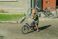 Den unga pojken på cykeln som nära väntar, shoppar Tobolsk Royaltyfri Bild