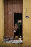 Den unga pojken plirar ut ur dörröppningen Royaltyfria Bilder