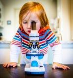 Den unga pojken ser till och med mikroskopet royaltyfria bilder