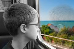 Den unga pojken ser ut ur fönstret av det gående drevet royaltyfri foto