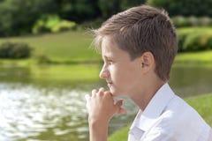 Den unga pojken sitter att ha tänkt i parkera Arkivfoto