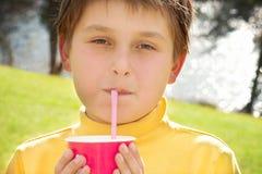 Den unga pojken som dricker jordgubben, mjölkar utomhus royaltyfria foton