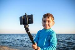 Den unga pojken som gör en selfie på stranden, lurar lyckligt och att le looen Royaltyfri Foto