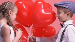 Den unga pojken som ger den blyga flickan, hjärta-formade ballonger, valentindaglyckönskan stock video