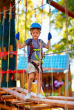 Den unga pojken som högt passerar kabelrutten bland träd, den extrema sporten i affärsföretag, parkerar Royaltyfri Foto